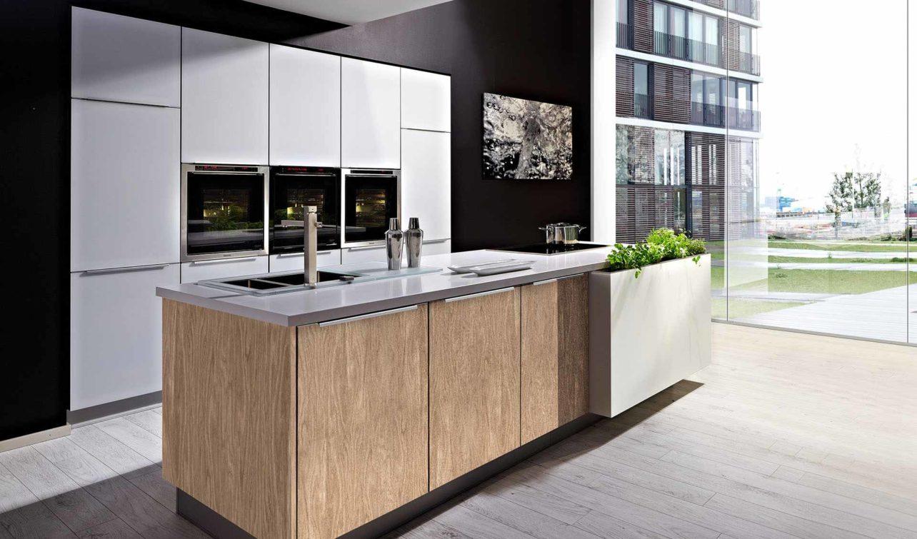 Massivholzküche Pure in Eiche edelweiß mit Fronten in weißem Glas, Hochschränke für E-Geräte und Kochinsel